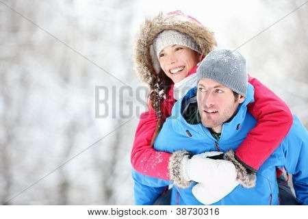 Happy Winter Reisen Paar. Man giving Woman piggyback Ride auf Winterurlaub im verschneiten Wald. Youn