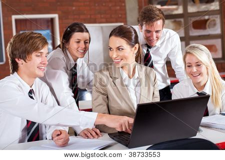 high school teacher and students with laptop in classroom