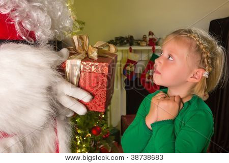 Little blonde girl receiving a red present from Santa Claus