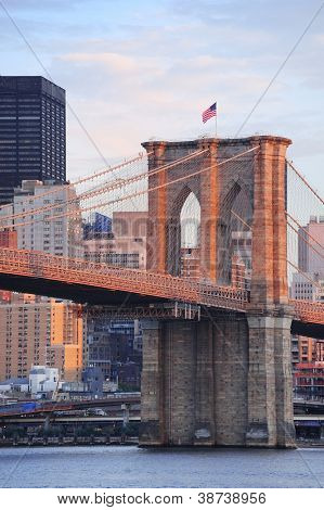 Brooklyn Bridge with lower Manhattan skyline in the morning with colorful cloud over East River in New York City