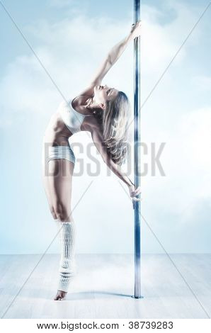 Jonge slank paal dans vrouw. Zachte blauwe en witte kleuren.