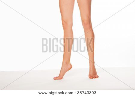 Cropped view image of a pair of shapely sexy female legs with beautiful smooth skin standing on tip toe over white with copyspace