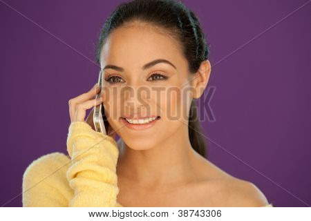 Beautiful brunette woman with a lovely smile talking on a mobile phone against a purple background