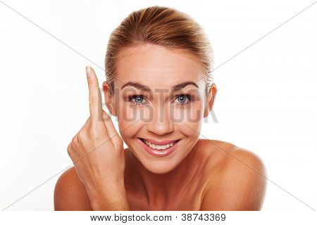 Beautiful blonde woman with a bright smile pointing above her head with her finger to blank copyspace isolated on white