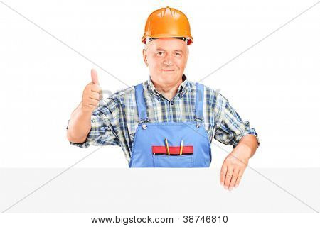 A male construction worker holding a panel and giving thumb up isolated on white background