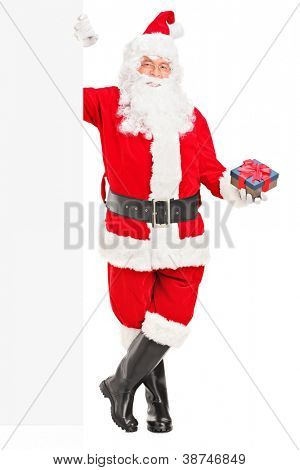 Full length portrait of a happy Santa claus standing next to a blank billboard and holding a gift isolated on white