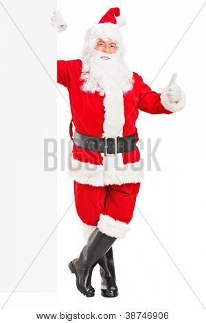 Full length portrait of a happy Santa claus standing next to a blank billboard and giving a thumb up