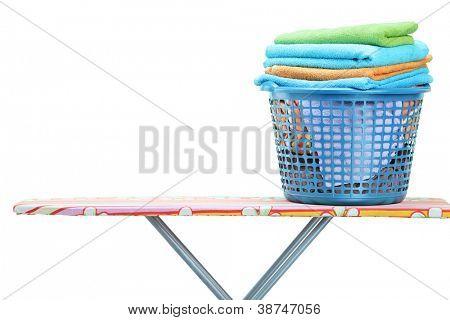 Um cesto de roupa cheio de roupa na tábua isolado no fundo branco