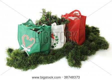 Overhead view of three reusable shopping bags filled with Christmas goodies and surrounded by green garland.  On a white background.