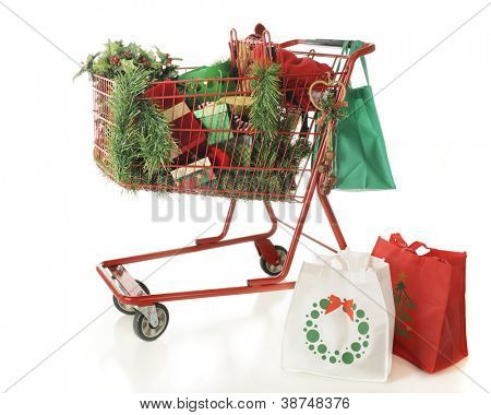 Three reusable shopping bags and a red shopping basket filled with Christmas shopping goodies.  On a white background.