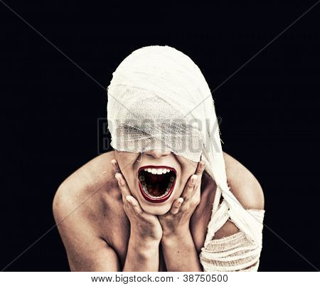 screaming woman  in bandage over black background (gothic style concept)