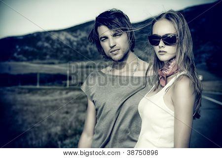 Paar der modernen Jugendlichen posiert auf einer Straße über malerische Landschaft.