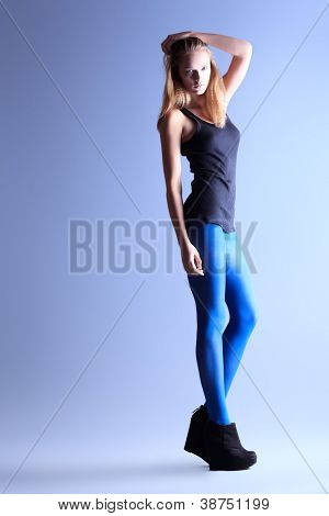 Full length portrait of an attractive young woman in fitting clothing posing at studio.