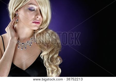 Beautiful woman with jewellery on dark background. Space for text.