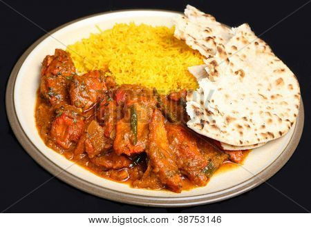 Indian chicken tikka jalfrezi curry meal with pilau rice and naan bread.