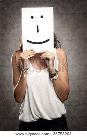 young woman holding smile symbol in front of her face