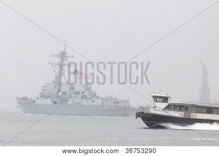 NEW YORK-OCT 9: A NY Waterway ferry passes as the USS Michael Murphy (DDG 112) departs New York Harbor, fully commissioned into active service, in rain and fog in New York on October 9, 2012.