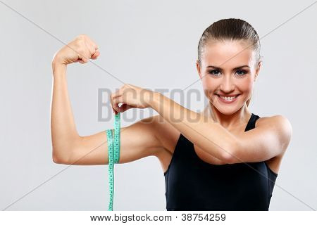 Beautiful fitness girl measure her biceps with a  ruler over grey background