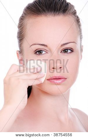 Young woman cleaning her face with cosmetic wad isolated on a white