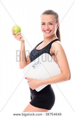 Happy woman with scales and green apple over white background