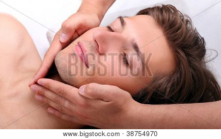 Closeup of Handsome man enjoying face massage in spa salon