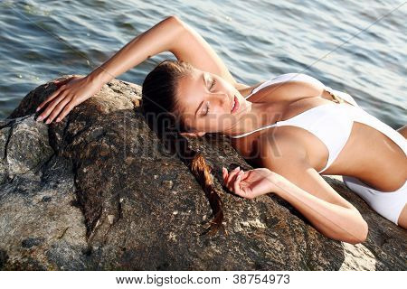 Sexy and attractive woman relaxing on the beach by the sea