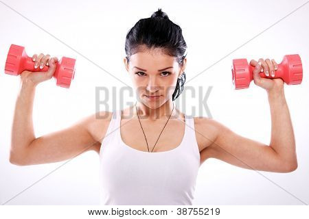 Cute and serious fitness girl lifting red dumbbells