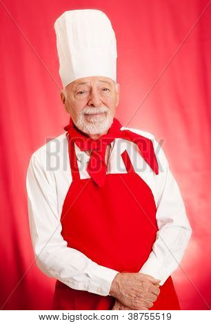 Portrait of handsome chef taken against a red background.
