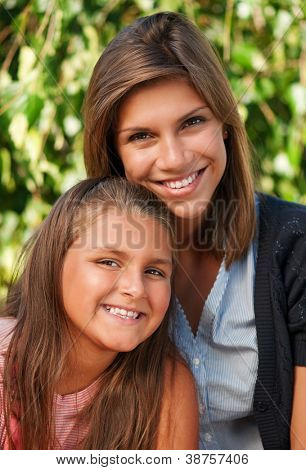Portrait of happy two sisters in park outdoors