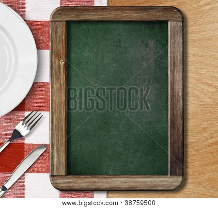 Menu blackboard lying on table with plate, knife and fork