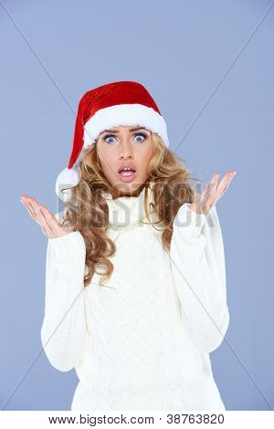 Sexy woman in Santa hat with hands raised, confused
