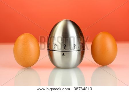 egg timer and eggs on red background