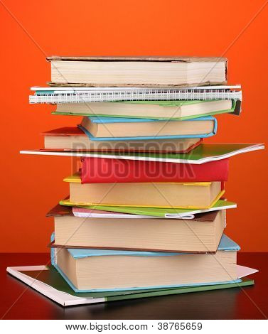 Stack of interesting books and magazines on wooden table on red background