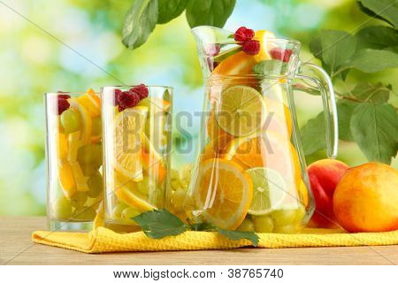 jar and glasses with citrus fruits and raspberries, on green background