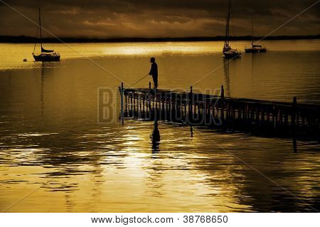 Dock floating in lake with sky and fisherman