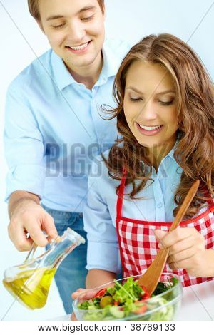 Happy man pouring oil into vegetable salad while his wife mixing ingredients