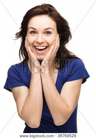 Young woman is holding her face in astonishment, isolated over white