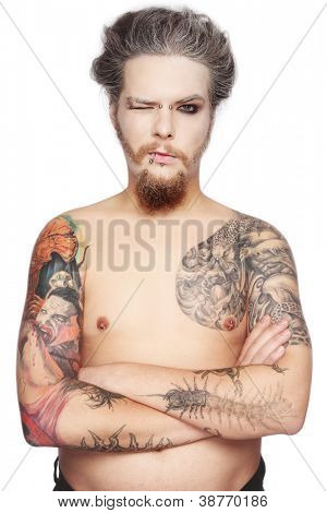 Man with tattoos and piercing over white background