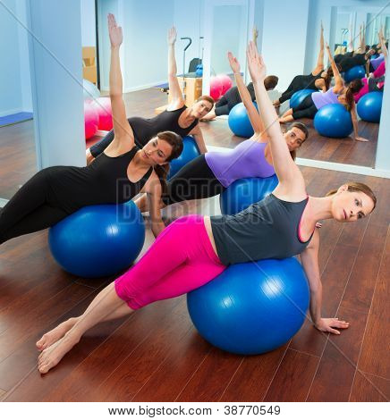 Pilates aerobics women group with stability ball in a row on mirror gym