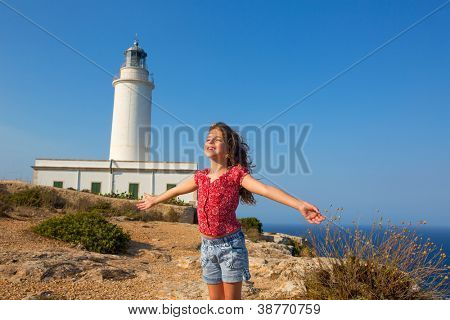 blue day with kid girl open hands to the wind in la Mola lighthouse of Formentera