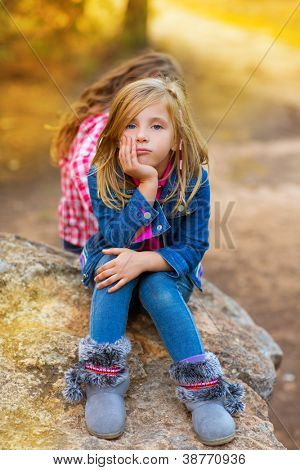blond kid girl pensive bored expression in the forest outdoor sitting on a rock