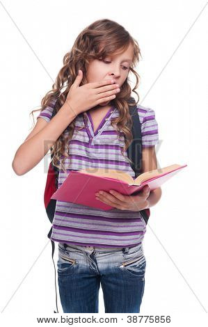 little girl reading book and yawning. studio shot over white background
