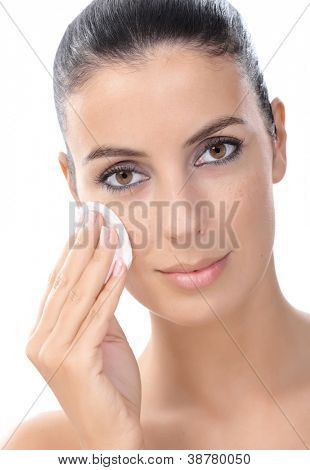 Closeup portrait of young attractive woman removing makeup by cotton pad.