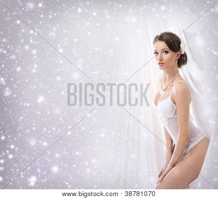 Young sexy bride in erotic lingerie over Christmas background