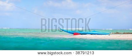 Blue kayak on an exotic pink sand beach