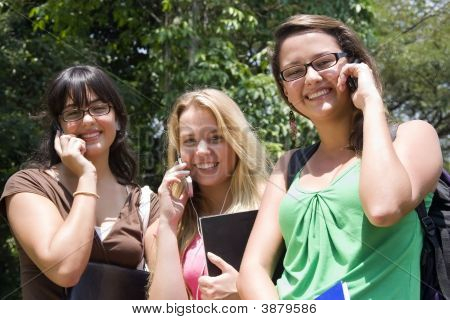 Three Women Speaking On Their Mobile Phone