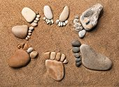 stock photo of barefoot  - trace feet of a pebble stone on the sea sand backdrop  - JPG