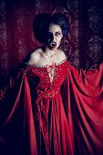 Portrait of a bloodthirsty female vampire over red vintage background. poster