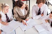 stock photo of tutor  - high school teacher tutoring group of students in classroom - JPG