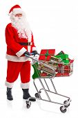 Santa Claus doing his Christmas shopping with a trolley full of gift wrapped presents, isolated on a